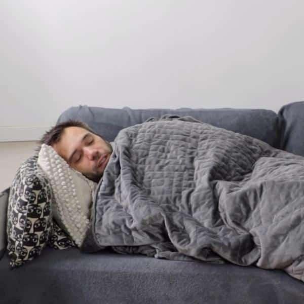 un homme emmitouflé dans sa couverture lestée